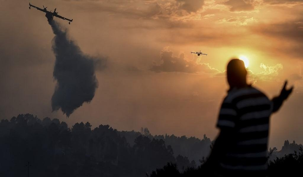 Ir para  <p>Mais de mil bombeiros e 14 aeronaves tentam conter um grande inc&ecirc;ndio florestal que castiga o centro de Portugal, na mesma regi&atilde;o onde dezenas de pessoas morreram em 2017. O vento e as altas temperaturas, que nessa...